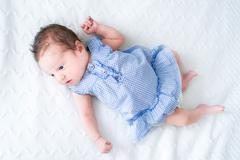 Adorable tiny newborn baby girl in a blue dress on a white knitted blanket Stock Photos