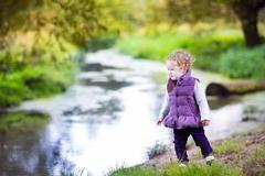 Beautiful little baby girl walking on a river shore on a nice autumn day Stock Photos