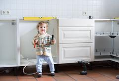 Little baby helping to assemble a kitchen in a new home - stock photo