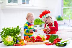 Children preparing healthy vegetable lunch Stock Photos
