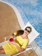 Woman wearing sunglasses on sun bed - stock photo