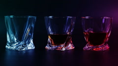Whiskey being poured into a glass against black background. Long shot. - stock footage