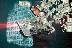 Composite image of hacker holding laptop and credir card Stock Photos