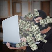 Composite image of focused burglar with balaclava holding laptop - stock photo