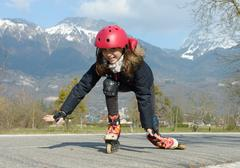 Pretty preteen girl on roller skates in helmet at a track Stock Photos