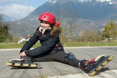preteen girl in rollerskate sitting on the road - stock photo