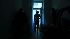 Man in apartment coming out of dark room to balcony Stock Footage