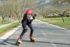 pretty preteen girl on roller skates in helmet at a track - stock photo