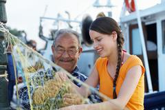 Young girl and fisherman - stock photo