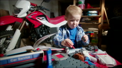Little Boy Dismantling Toy Car Stock Footage