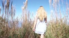 Adventurous Girl Model Joyfully Walks through Tall Grass Overlooking the Ocean Stock Footage