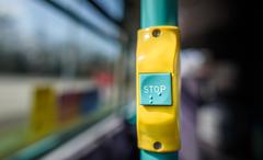A stop button on a public bus with additional braille. Stock Photos