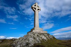 Celtic stone cross monument on a hill against a blue sky. Stock Photos