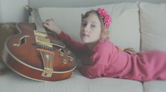 Little girl is playing the guitar at the couch at home Stock Footage