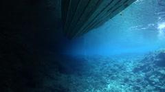 Ocean scenery slow tilt up from diver swimming below up to show Solomon Islander Stock Footage