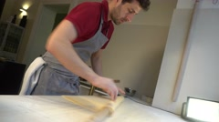 Using rolling pin to create a round piece of dough - stock footage