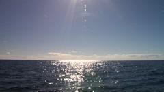 Ocean scenery sun shining on ocean surface, big slow swell but calm seas, sun - stock footage