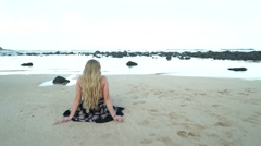 Beautiful Blond Girl Model Wearing Dress Sits on a Beach in Hawaii Stock Footage