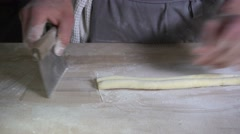 Human hands cutting rolled dough into little shapes - stock footage