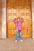Schoolgirl posing before big wooden door - stock photo