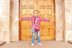 Schoolgirl before big wooden door - stock photo