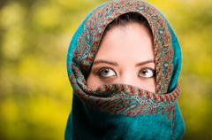 Woman wearing blue, grey and brown coloured scarf covering face only revealing - stock photo
