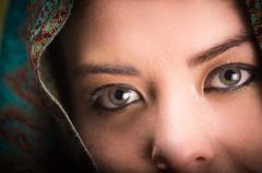 Closeup woman wearing blue, grey and brown coloured scarf covering head only - stock photo