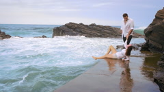 Young couple leaning sitting at tidal pool kissing with waves crashing behind Stock Footage
