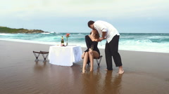 Romantic couple kissing on beach with table and chairs Arkistovideo