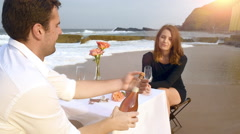 Young romantic couple popping and drainking champagne at a table on the beach Stock Footage