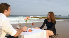 Handsome young man proposes to attractive girlfriend on the beach Stock Footage