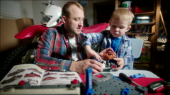 Father and Son Assembling the Toy Car from Parts Stock Footage
