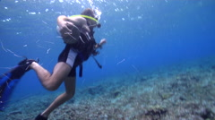 Male model scuba diver swimming on very shallow reef and surface in Solomon Stock Footage