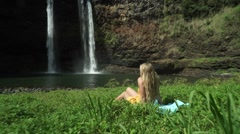 Beautiful Girl Model Sits in Grass Looking at Scenic Waterfall in Paradise Stock Footage