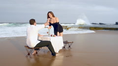 Young couple toasting new engagement on beach with champagne Stock Footage