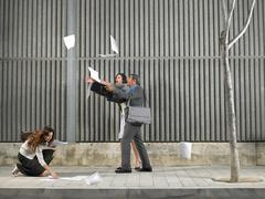 Older man and young woman chasing papers Stock Photos