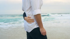 Young couple walking along beach, girl with arm around guy's waist. Stock Footage