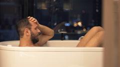 Sad, unhappy man crying during bath in bathtub at night Stock Footage