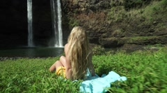 Beautiful Island Girl Model Sits in Grass by Tropical Hawaiian Waterfall - stock footage