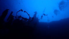 Distant group of scuba divers swimming on wreckage in Solomon Islands, HD, Stock Footage