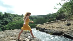 Beautiful Young Girl Model Walks Playfully Past Guitar and Jumps Over Stream Stock Footage