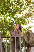 Woman with eyes closed leans on railing Stock Photos