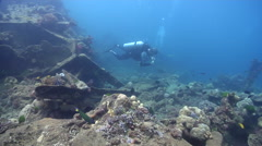 Expert diver with perfect buoyancy swimming on wreckage in Solomon Islands, HD, Stock Footage