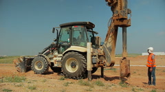 Tractor lifts a steel rod and put it in a hole in the ground - stock footage