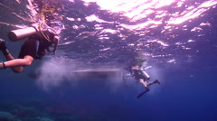 Ocean scenery one diver passing up fins and climbing ladder, three others Stock Footage