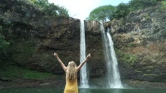 Girl Model Holds up Arms in Front of Tropical Hawaiian Waterfall - stock footage