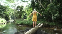 Young Girl Model Wearing Yellow Dress and Sun Hat Walks Barefoot over Log Stock Footage