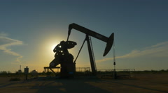 Industrial jack pump platform pumping crude oil over sunset sun - stock footage