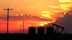 Oil pump jack containers and electrical wiring at amazing golden sunset Stock Footage