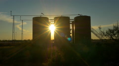 Sunset sun shining through big oil pump and oil reservoir containers - stock footage